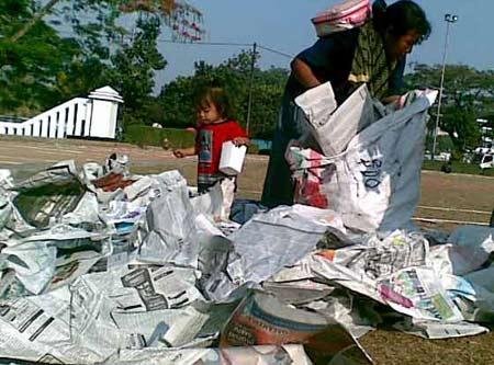 Mengemas sampah kertas koran.