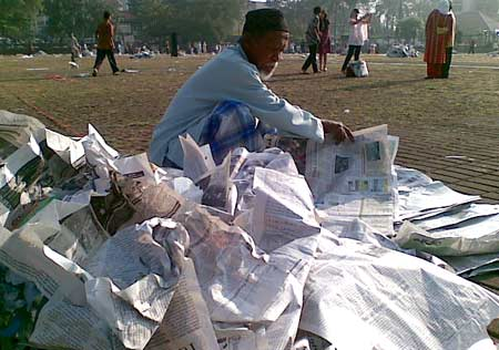 Merapikan sampah kertas koran.