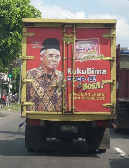 Gambar mbah Marijan di satu bak truk di jalan raya.
