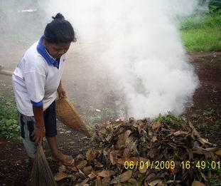 Ibu-ibu membakar sampah kebun di halaman.