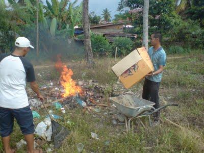 Bapak-bapak membakar sampah hasil kerja bakti lingkungan.
