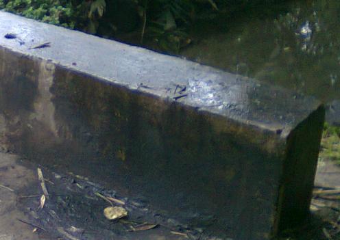 Bahu jembatan hitam dan basah karena dilumuri oli bekas.
